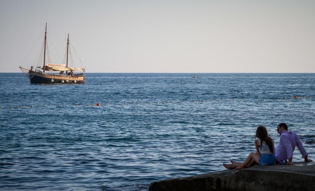 Couple overlooking ship on Adriatic