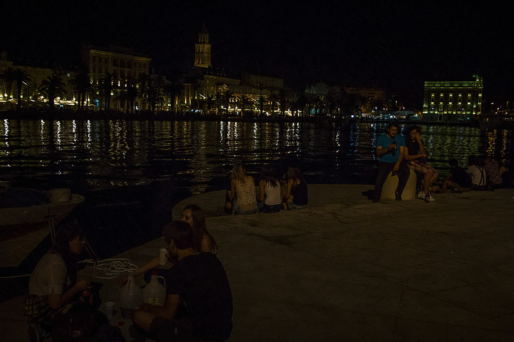 Tourist and Locals in Split Croatia drinking by the water at night
