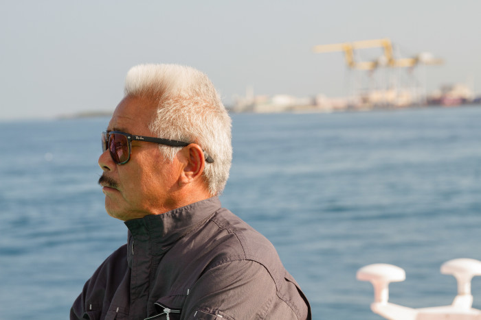Okinawan Ship Worker keeps watch on boat